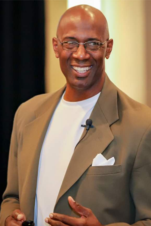 Anthony Griggs Smiling in a brown jacket.