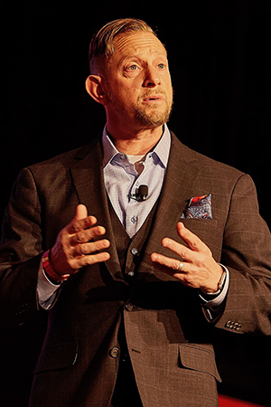 Matthew S Newman in a brown jacket and blue shirt with his hands in front of him.