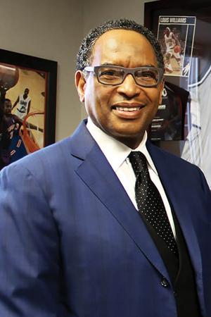 NBA Reggie Wilkes in a blue jacket and black tie, smiling.