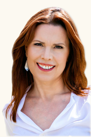 Annie Duke in a white shirt, smiling.