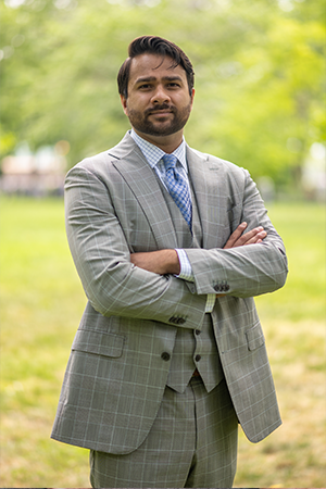 Cyber Security Expert Prashanth Challa in a grey jacket and blue shirt with his arms folded.