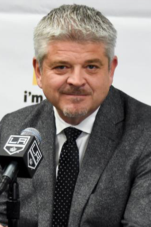 NHL Coach Todd Mclellan in a grey jacket and black tie, giving an interview into a microphone in front of him.