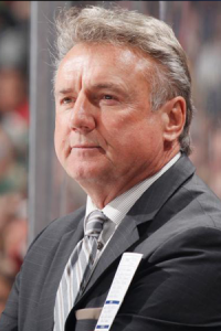 NHL Coach Rick Bowness in a black jacket and tie at a game,