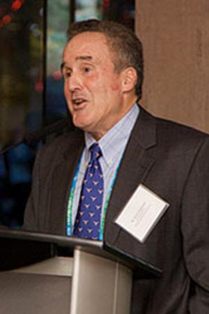 Dr. Steven Ugerleider giving a keynote speech in a black jacket and purple tie.