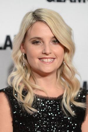 Erin Merryn in a black dress, smiling.