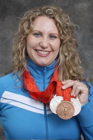 Olympian Keynote Speaker Margaret Hoelzer smiling and holding her medals.