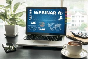 """A laptop screen that displays """"WEBINAR,"""" an intro screen for a virtual event."""