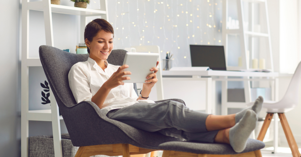 A person smiling, sitting in a chair with their legs on a stool, comfortably attending a virtual meeting on their tablet.