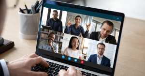 hands on laptop displaying a virtual meeting with six people