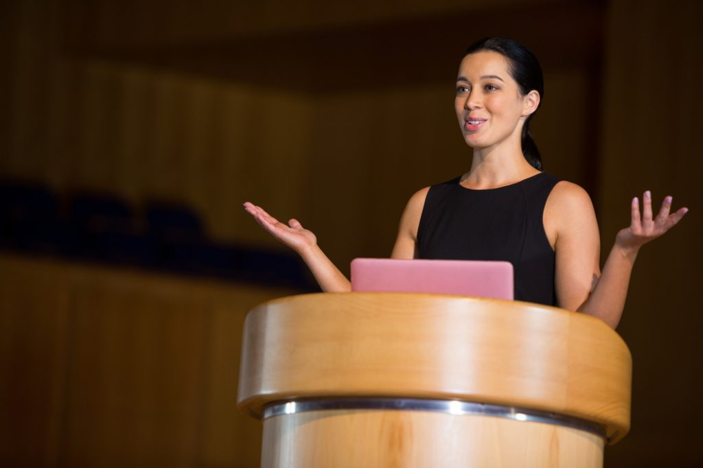 A woman woman with her arms spread at a podium giving a motivational speech
